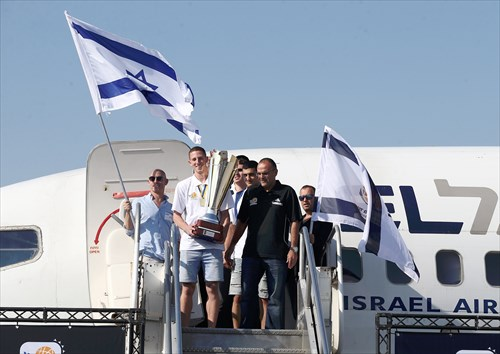 Captain Gil Aharon Beni leaves the plane first, carrying the champions' trophy